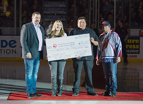 Terry Huisman, Business Manager for the Lethbridge Hurricanes (left) presents a cheque in the amount of $26,000+ to, Janelle Marietta-Vasquez, Director Operations for United Way, and United Way raffle volunteers  Harley No-Runner and Terry Eaglespeaker. Photo by Erica Perreaux (@perreauxphoto)